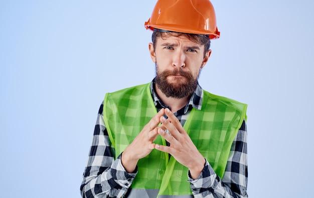 Emotional builder pokazuje rękami pomarańczową kamizelkę odblaskową hełmu