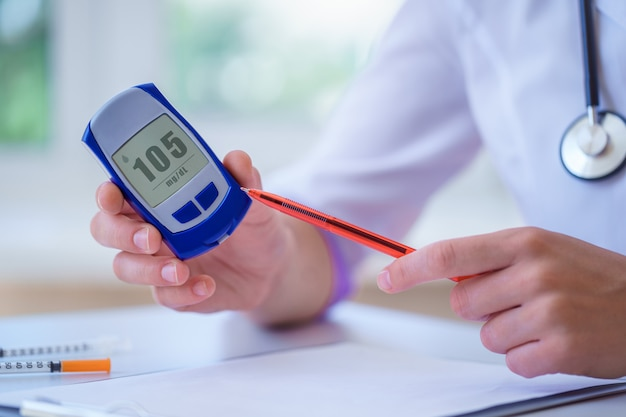 Endokrynolog pokazuje pacjentowi z cukrzycą glukometr z poziomem glukozy we krwi podczas konsultacji lekarskiej i badania w szpitalu. cukrzycowy styl życia i opieka zdrowotna