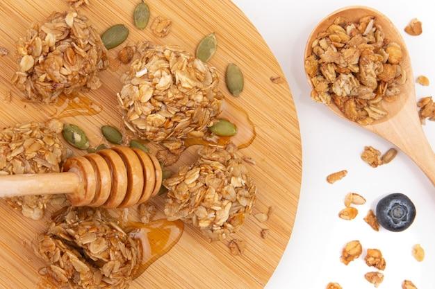 Energetyczna granola gryzie z miodem na drewnianym talerzu.