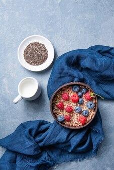 Energetyczna granola z malinami, jagodami i mlekiem do kokosowej miski na niebiesko