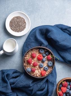 Energetyczna granola z malinami, jagodami, nasionami chia i wegańskim mlekiem w kokosowej misce na niebieskim tle. widok z góry