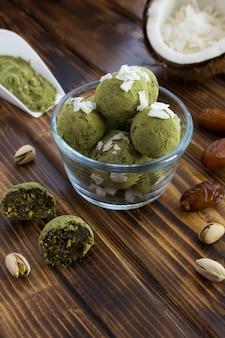 Energetyczne kulki z matchą w proszku, pistacjami, daktylami i wiórkami kokosowymi w szklanej misce na brązowym drewnianym stole.