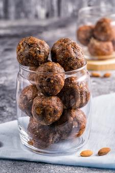 Energetyczne piłki wysuszone owoc i dokrętki w szklanym słoju, sellative ostrość na tle.