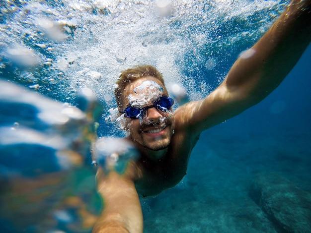 Energia człowieka z uśmiechem robienie zdjęć selfie pod wodą latem.