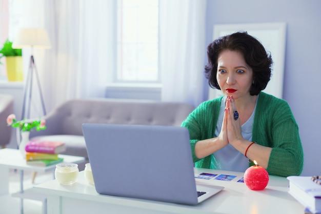 Energia duchowa. przyjemna miła kobieta składająca ręce razem, patrząc na ekran komputera