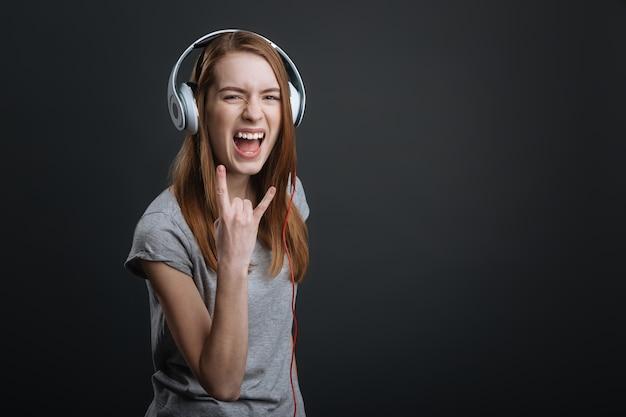 Energia dźwięku. kreatywna artystyczna urocza pani testująca niedawno zakupione urządzenie do słuchania swojej muzyki i wyglądania emocjonalnie
