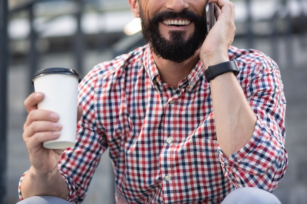 Energia kawy. przyjemny uśmiechnięty mężczyzna rozmawia przez telefon, ciesząc się swoim ulubionym napojem