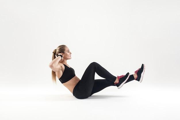Energia młoda dorosła kobieta robi treningu, ćwiczenia crossfit. strzał w pomieszczeniu, szare tło