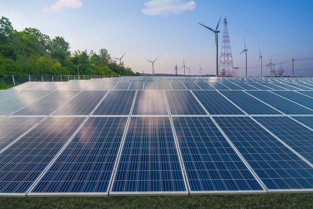 Energia odnawialna, panele słoneczne i turbiny wiatrowe na zielonej trawie w błękitne niebo