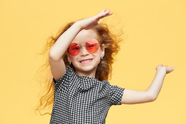 Energiczna, aktywna, wesoła dziewczynka z falującymi rudymi włosami, wyglądająca z szerokim promiennym uśmiechem, miło spędzająca czas