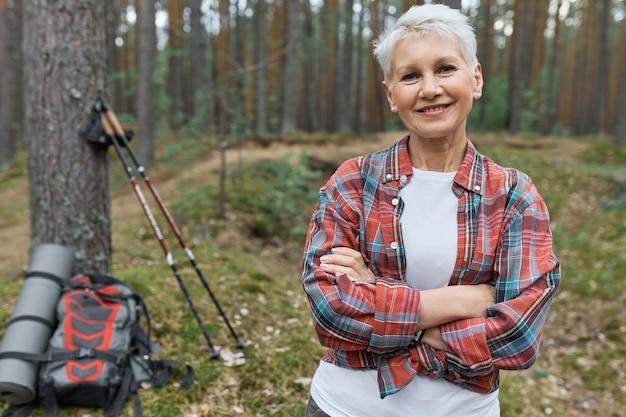 Energiczna atrakcyjna turystka w średnim wieku pozuje na zewnątrz, wybiera aktywny tryb życia, podróżuje samotnie z plecakiem i kijkami do nordic walking, trzymając ręce skrzyżowane i uśmiechając się do kamery