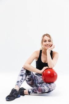Energiczna blond kobieta w wieku 20 lat ubrana w odzież sportową, ćwicząca i wykonująca ćwiczenia z piłką fitness podczas aerobiku na białym tle nad białą ścianą
