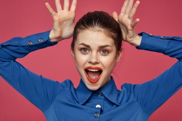 Energiczna kobieta gestykuluje rękami w pobliżu twarzy i niebieskiej koszuli różowym tle