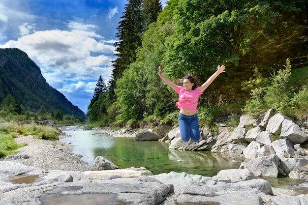 Energiczna młoda dziewczyna świętująca swoją wolność, skacząca w powietrzu z wyciągniętymi ramionami na skałach wzdłuż rzeki w górskiej dolinie