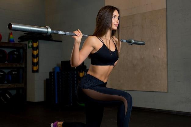 Energiczna młoda kobieta w ciekawych sportowych leginsach i czarnej topie ćwiczy na siłowni wypady ze sztangą.