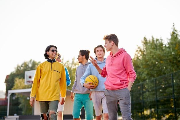 Energiczne, zdrowe nastolatki bawią się, rozmawiają przed grą w koszykówkę