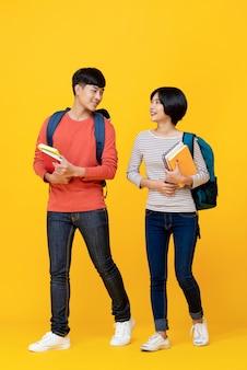 Energiczni studenci azjatyccy chodzą i rozmawiają ze sobą