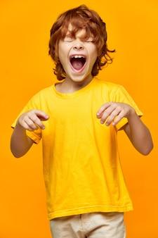 Energiczny chłopiec o rudych włosach szeroko otworzył usta i zmrużył oczy