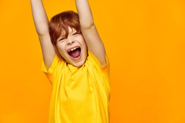 Energiczny chłopiec o rudych włosach uniósł ręce i szeroko otworzył usta