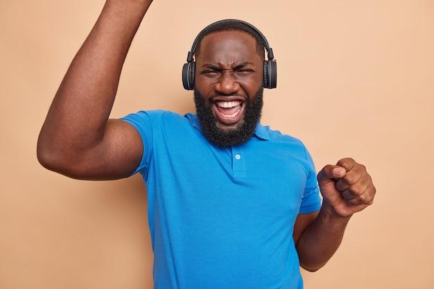 Energiczny facet słucha muzyki online śpiewa i mruży twarz porusza się w rytm piosenki używa bezprzewodowych słuchawek ubrany w casualową niebieską koszulkę lubi nową playlistę na beżowej ścianie