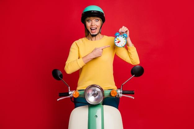 Energiczny kierowca szalonej dziewczyny jedzie motorowerem punkt palec wskazujący zegarek otwarte usta