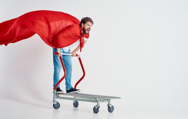Energiczny kurier w czerwonym płaszczu przeciwdeszczowym stoi na wózku towarowym w jasnym pomieszczeniu