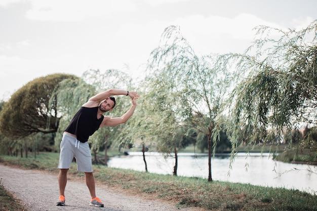 Energiczny młody człowiek ćwiczy na świeżym powietrzu w parku, aby zachować dobrą kondycję ciała.