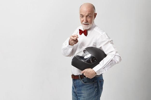 Energiczny pewny siebie starszy dojrzały europejczyk z siwą brodą, wskazując palcem na aparat