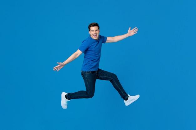 Energiczny przystojny mężczyzna skacze i uśmiecha się z wyciągniętymi rękami