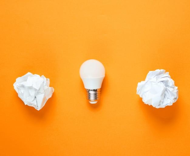 Energooszczędna żarówka i zmięte kulki papieru na pomarańczowym tle. minimalistyczna koncepcja biznesowa, pomysł. widok z góry