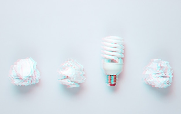 Energooszczędna żarówka i zmięte papierowe kulki na szarym tle. efekt usterki. widok z góry