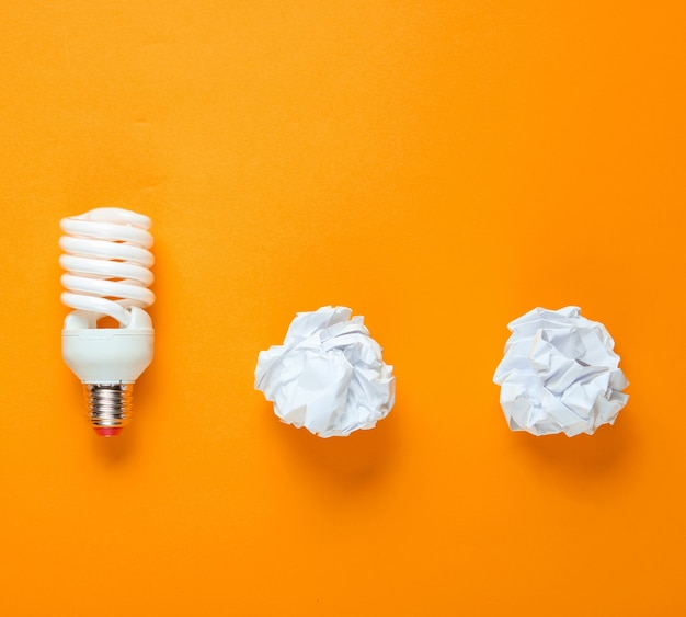 Energooszczędna żarówka i zmięte papierowe kulki na żółtym tle. minimalistyczna koncepcja biznesowa, pomysł. widok z góry