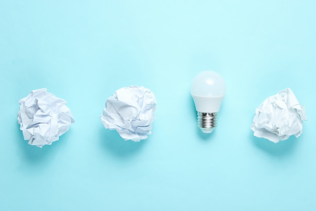 Energooszczędna żarówka i zmięte papierowe piłki na błękitnym stole. minimalistyczna koncepcja biznesowa, pomysł. widok z góry