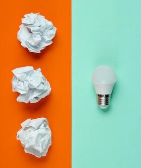 Energooszczędna żarówka led i zmięte kulki papieru na pomarańczowo-niebieskim tle. minimalistyczna koncepcja biznesowa, pomysł. widok z góry