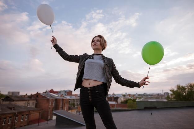 Enigmatyczna młoda kobieta z dwoma zabawkami balonami. rozmarzona i infantylna osobowość, lekkość i nadzieja, lot do marzeń i bogata koncepcja wyobraźni. tło miasta uban, wolna przestrzeń