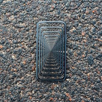 Enigmatyczna surrealistyczna iluzja optyczna. zbliżenie: smartfon na mokrym asfalcie.