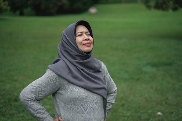 Enior muzułmanka relaksujący, biorąc głęboki oddech i rozciągając
