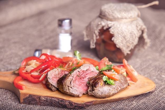 Entrecot z warzywami na drewnianym stole. stonowane zdjęcie