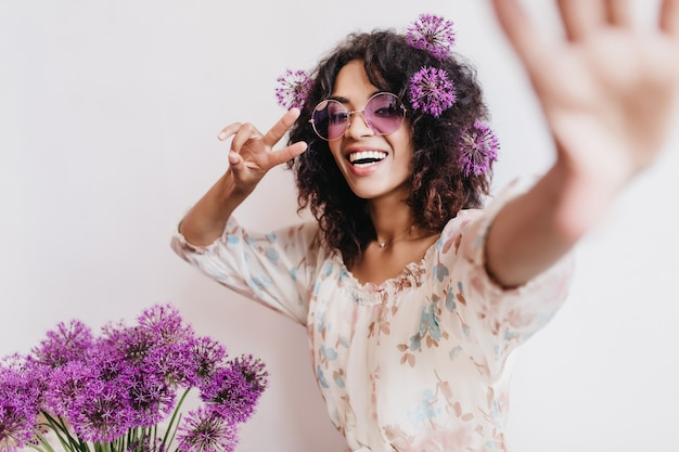 Entuzjastyczna afrykańska dziewczyna w stylowej sukience robi selfie z sojusznikami. spektakularna czarna młoda kobieta bawi się podczas sesji zdjęciowej z fioletowymi kwiatami.