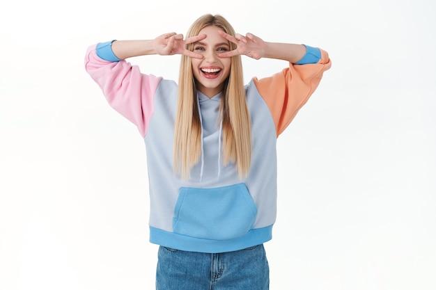Entuzjastyczna, atrakcyjna młoda dziewczyna w bluzie z kapturem, pokazująca znaki pokoju nad oczami, śmiejąca się i uśmiechnięta