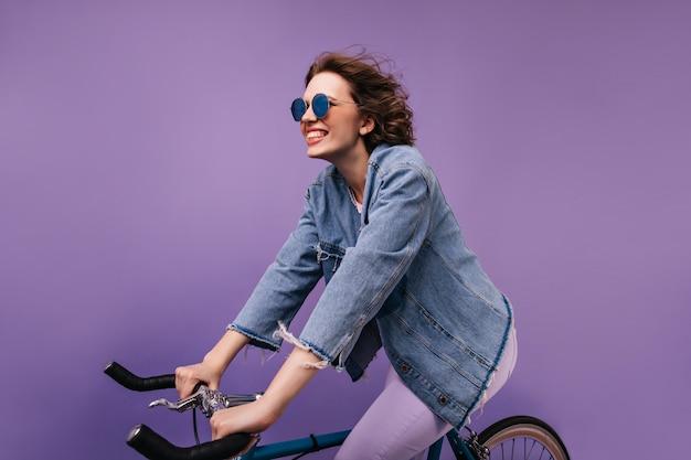 Entuzjastyczna bawiąca się rowerzystka. całkiem kaukaski dziewczyna siedzi na rowerze i robi śmieszne miny.