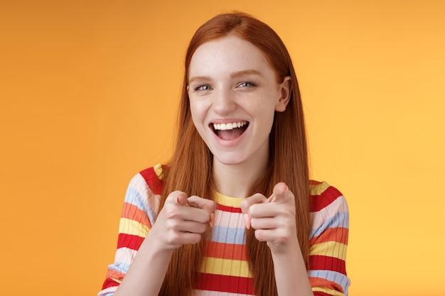 Entuzjastyczna beztroska sympatyczna rudowłosa dziewczyna wskazująca palcem-pistolety aparat uśmiechający się radośnie gratulujący przyjacielowi niesamowity wybór bezczelny powitanie podpowiadająca dziewczyna złapana dobra okazja