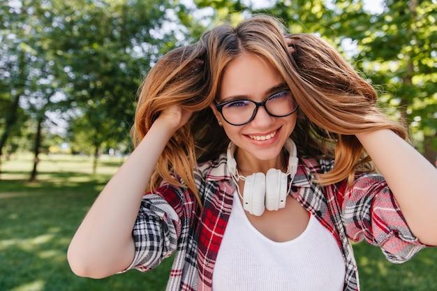 Entuzjastyczna biała kobieta bawi się włosami w parku. zewnątrz zdjęcie uroczej kobiety rasy kaukaskiej w okularach pozowanie w słuchawkach w letni poranek.