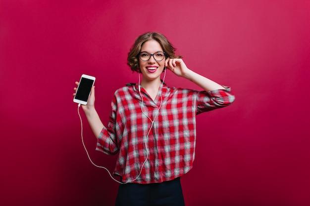 Entuzjastyczna biała modelka z modną krótką fryzurą pozuje z telefonem elegancka dziewczyna w bordowej koszuli w kratkę trzymając smartfon.