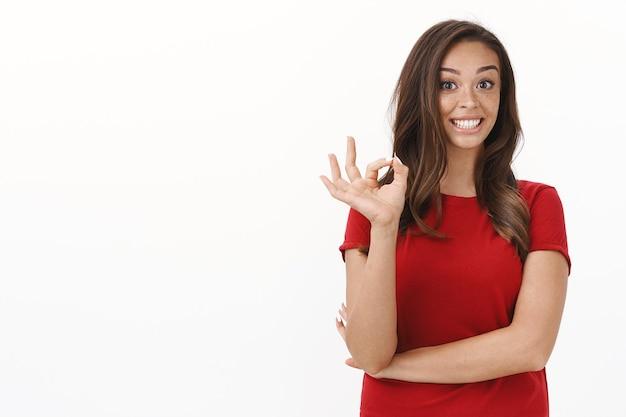 Entuzjastyczna brunetka kaukaska kobieta w czerwonej koszulce uśmiecha się radośnie, optymistycznie słyszy doskonały pomysł, pokazuje znak zgody, powiedz ok zgadzam się, weź udział w ciekawym wydarzeniu, stojąc na białej ścianie