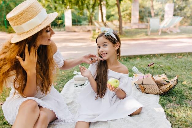Entuzjastyczna dziewczyna z długimi brązowymi włosami trzymająca zielone jabłko i rozmawiająca z mamą. ładna kobieta w elegancki kapelusz dotykając twarzy córki palcem siedząc na kocu w parku.