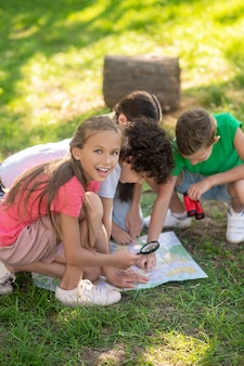 Entuzjastyczna dziewczyna z lupą i przyjaciółmi z mapą