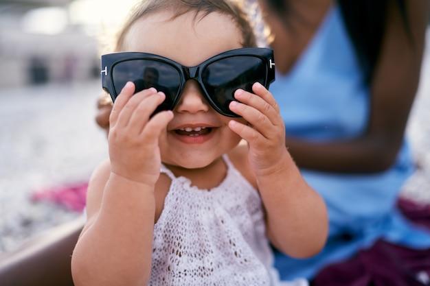 Entuzjastyczna dziewczynka trzymająca w dłoniach duże okulary przeciwsłoneczne