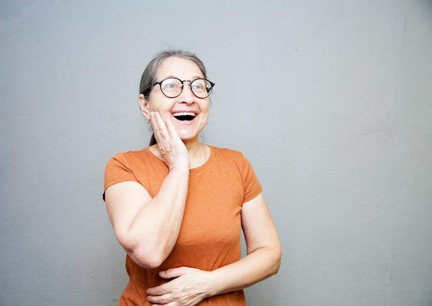 Entuzjastyczna i zdziwiona starsza kobieta w brązowej koszulce na szarej ścianie