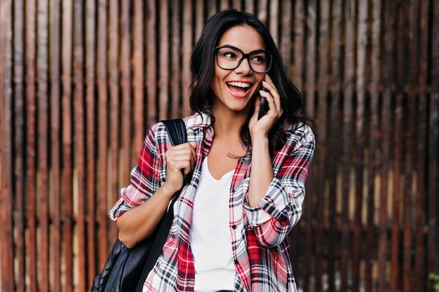 Entuzjastyczna kaukaski dziewczyna w okularach rozmawia przez telefon z uśmiechem. zewnątrz portret blithesome brunetka kobieta z skórzanym plecakiem.